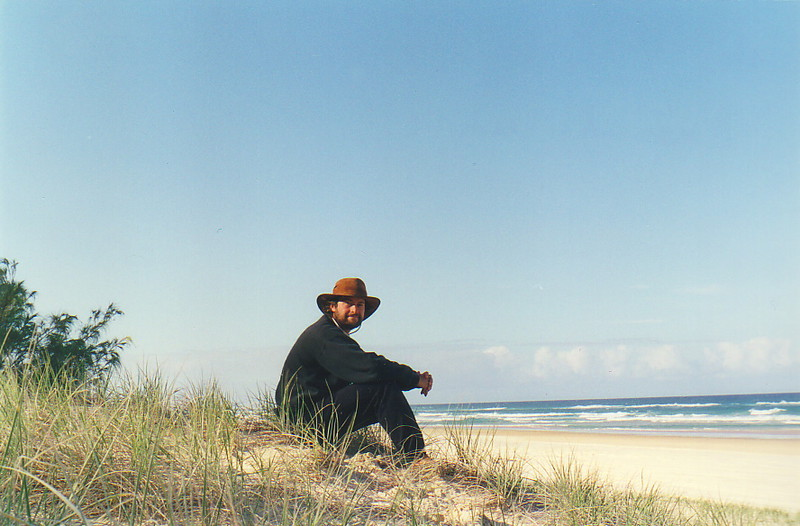 Mark sitting on a beach