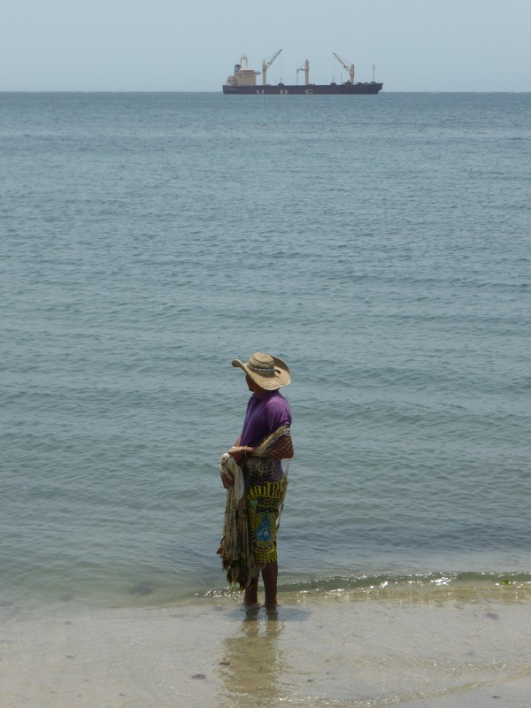 A man fishing in Santa Marta with a container ship in the background