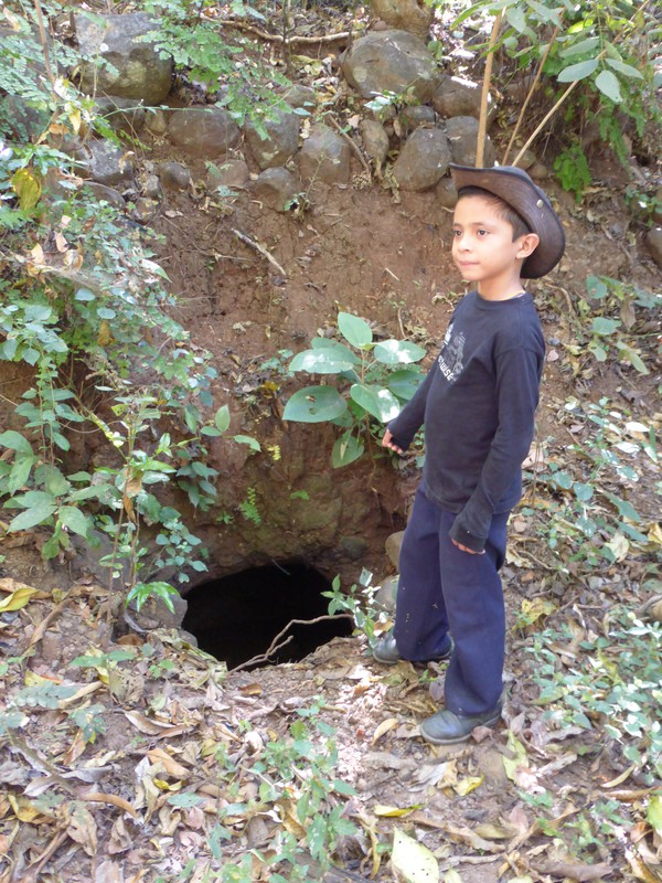 Nelsito pointing to a hole that locals used to shelter from the bombs