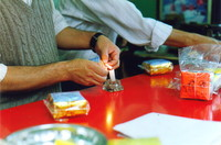 A tea vendor sealing tea packets with a candle
