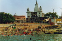 People washing themselves by a temple on the Ganges