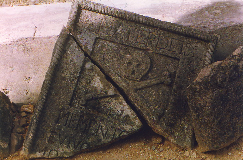 A carved stone slab with a skull and crossbones on it