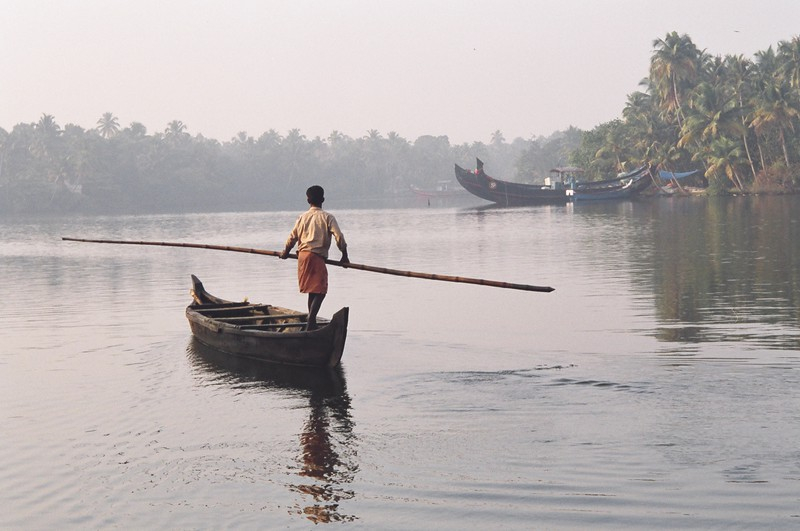 A man punting a canoe along the backwaters