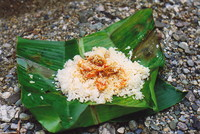 A meal of prawns and rice in a banana leaf