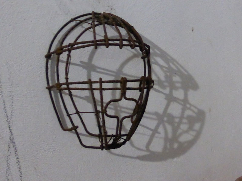 An iron head mask on the hotel wall