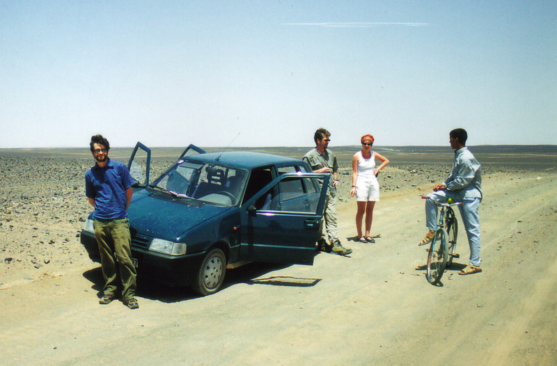 Mark and two hitchers talking to a man on a bicycle