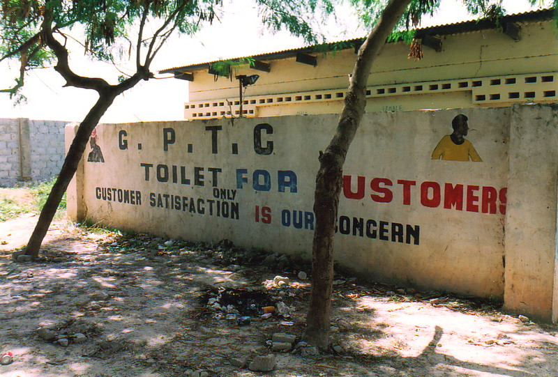 A Gambian toilet with a sign saying 'Customer Satisfaction is Our Concern'