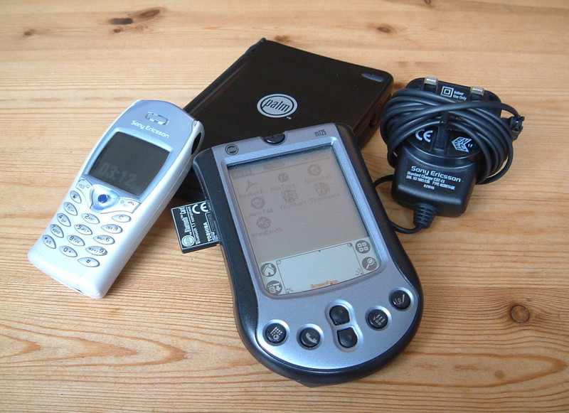 A Sony Ericsson mobile phone and mains adaptor, a Palm m125 and a fold-out keyboard